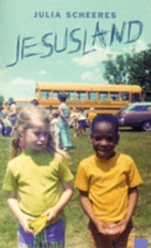 A white little girl standing with a black little boy in front of a school bus.