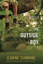 Boy's legs dangling from a branch.