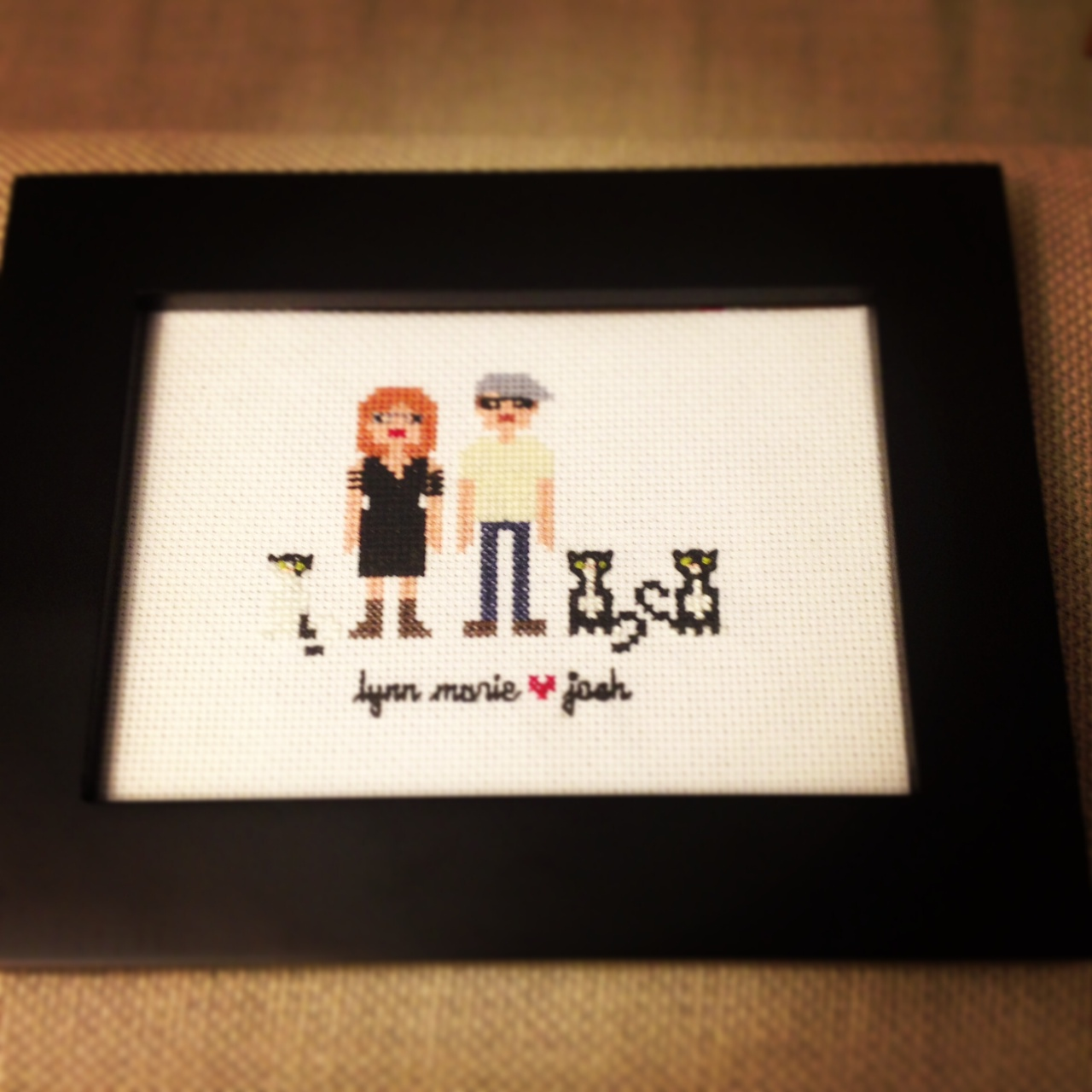 Lynn Marie and Josh as pixel people, cross-stitch