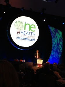 "A tanned, white man standing in front of a blue background with a white moon-shape that says ""One Health"" on it behind him."