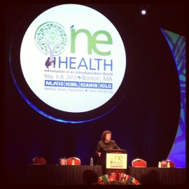 A woman dressed in black standing at a podium in front of a white lighted circle stating One Health.