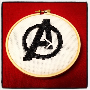 Avengers logo cross-stitched in black and framed in a wooden hoop.
