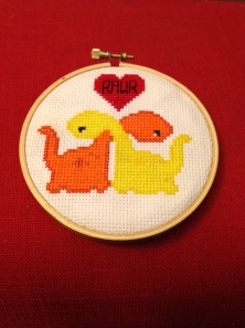 "Cross-stitch of two dinosuars hugging with their necks. A red heart above their heads says ""Rawr"""
