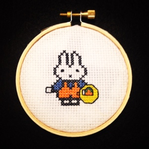 A cross stitch of a bunny holding a basket of carrots