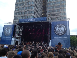 A stage surrounded by blue signs with a dog in a suit and the words Boston Calling. A band is on the stage and a large crowd is in front of them.