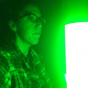 A woman in a flannel shirt looks directly into a glowing green light