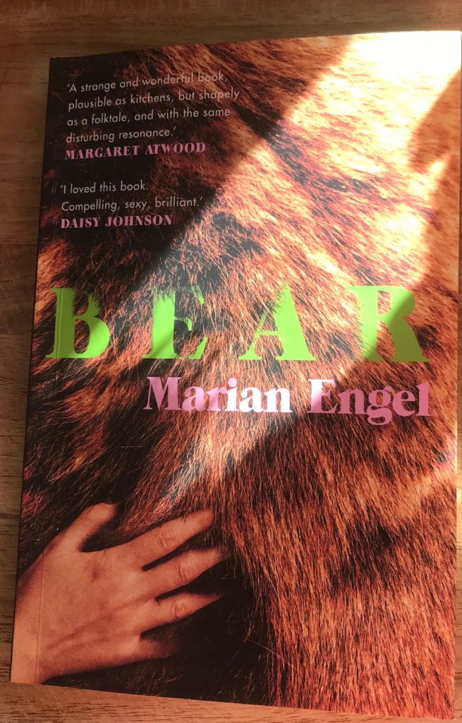 Photo of a physical book cover. The word BEAR in neon green font is on top of the coat of a bear with a woman's hand running through the fur.